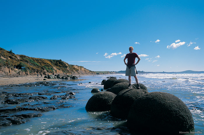 Tourist standing on the moeraki boulders